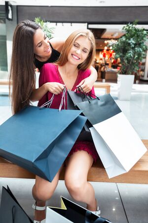 acquired: The girls enjoy the acquired shopping in the store. Its a very happy day