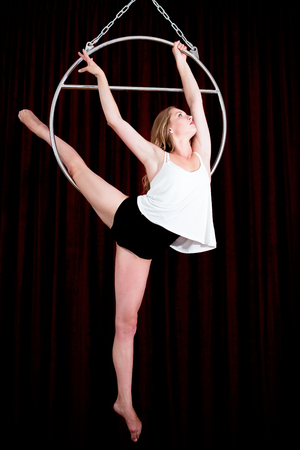 trapeze: The blonde girl is showing a trick on the air ring. She love to dance Stock Photo