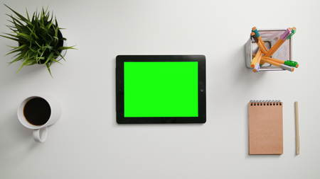 A mans finger touching an i-Pad with a green screen. A tablet is on the white table. View from the top. Close-up. Stock Photo