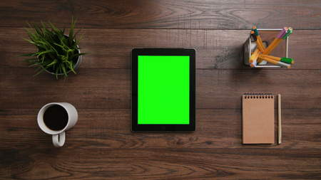 A mans finger touching an i-Pad with a green screen. The i-Pad is on the brown table. View from the top. Close-up. Stock Photo