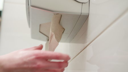 A hand picking a paper towel in the bathroom. Close-up shot Фото со стока