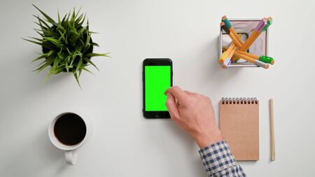 Lublin, Poland - November 2017: A man's finger touching a smartphone with a green screen. The phone is on the white table. View from the top. Close-up.