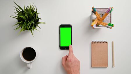 Lublin, Poland - November 2017: A man's finger scrolling on the smartphone with the green screen. The phone is on the white table. View from the top. Close-up. Editorial