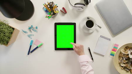 A finger scrolling on a tablet with a green screen. The tablet is on the white table. View from the top. Close-up.