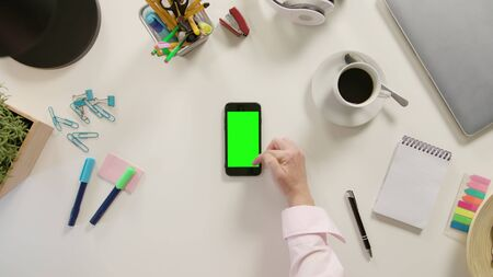 Lublin, Poland - November 2017: A finger scrolling on a phone with a green screen. The phone is on the white table. View from the top. Close-up.