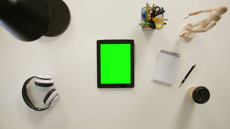 A finger zooming in on a tablet with a green screen. The tablet is on the white table. View from the top. Close-up.