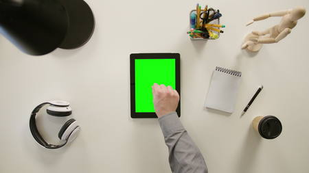 A finger zooming out on a tablet with a green screen. The tablet is on the white table. View from the top. Close-up. Stok Fotoğraf
