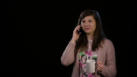 An attractive young lady wearing a pink sweater using a phone and holding a cup against a black background. Medium shot