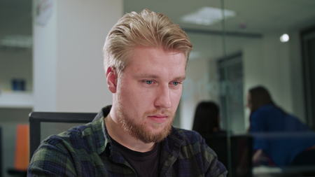 A young blonde man working in an office. Close-up shot. Soft focus.