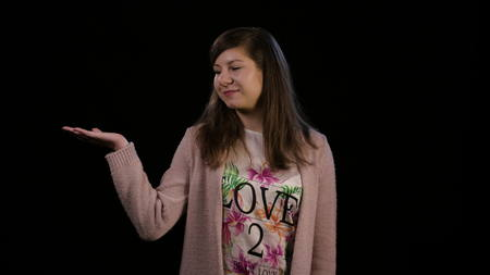 An attractive young lady wearing a pink sweater spreads out her arms against a black background. Offering a choice concept. Medium shot
