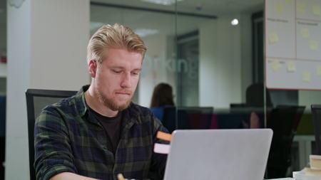 A young blonde man looking at the laptop indoors. Medium shot. Soft focus. Foto de archivo