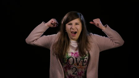An attractive young lady wearing a pink sweater with her arms up in the air rejoycing and feeling happy against a black background. Medium shot Foto de archivo