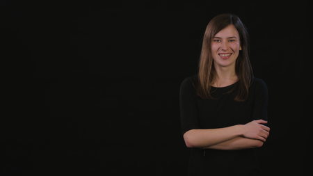 A beautiful young lady smiling and standing with her arms folded and pointing with her finger against a black background. Medium Shot Foto de archivo
