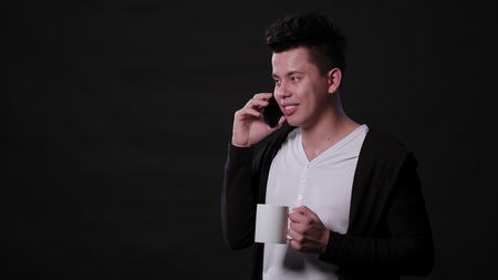 An attractive young man talking on the phone and holding a white cup against a black background. Medium Shot