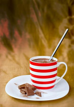 chocolate powder: Chocolate blocks, chocolate powder and hot chocolate drink in coffee cup on creative yellow-brown batik drapery