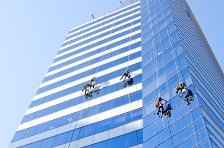 property management: Group of workers cleaning windows of a tall building at Santiago de Chile