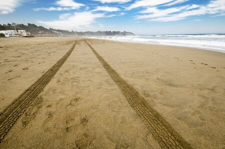 Shot of car tracks in the sand at the beach  photo