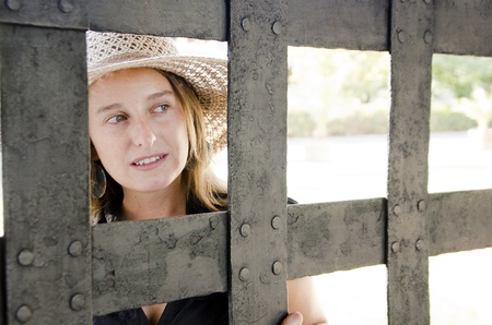 Beautiful young woman looks inside through a gate or cage. Stock Photo - 13238537