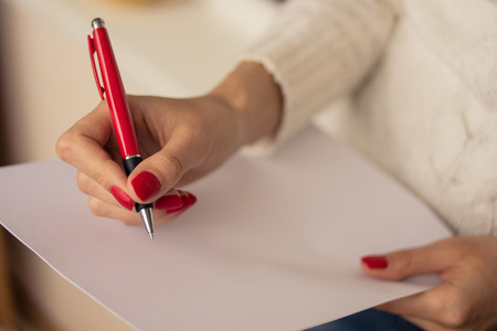 note paper: Female hands with red nails write on a sheet of paper Stock Photo