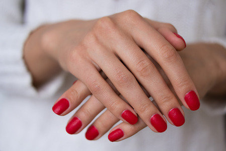 red nail colour: Female hands with red nails on a white background