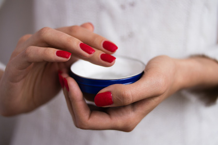 Female hands with red nails applied the cream out of the blue jar Stok Fotoğraf