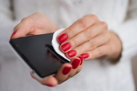 manos limpias: Cuidado y limpiar el tel�fono con un algod�n Foto de archivo