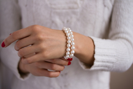 perlas: pulsera de perlas en una mano femenina