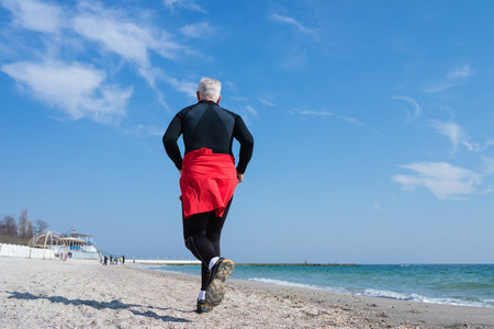 tracksuit: Gray-haired man runs along the beach tracksuit