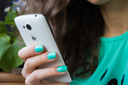 female hand with bright manicure holding a cell phone. in the picture prevails green, the models face is not visible Stok Fotoğraf