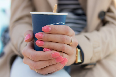 Blue paper Cup of coffee in female hands with pink manicure. The girl is dressed in a beige coat, striped t-shirt and blue jeans.