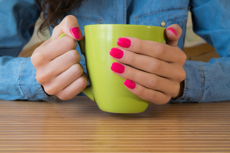 Girl in a denim shirt and red nail Polish sits at a wooden table and keeps a big green Cup Stok Fotoğraf