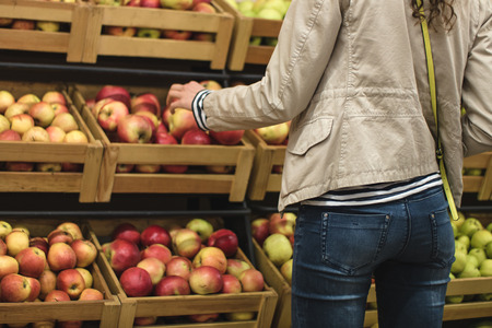 fresh apple: Girl in the beige jacket and blue jeans picks apples in the supermarket. Girl seen from the back. In the background you can see the boxes of apples. Stock Photo