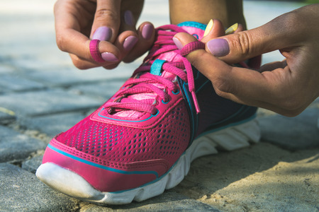 training shoes: Hands of a young woman lacing bright pink and blue sneakers. Shoes standing on the pavement of stones and sand. In female hands purpleyellow manicure. Photographed closeup.