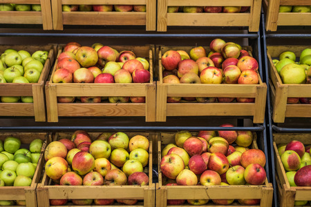 Organic apples in wooden boxes in the supermarket are sorted by varieties