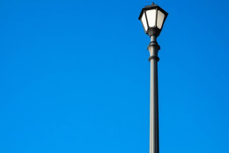 Street lamp on a bright blue background. Black lantern in vintage style, photographed in the morning sunshine. Bottom view. The object is to the right in the picture, the rest is free for your text. photo