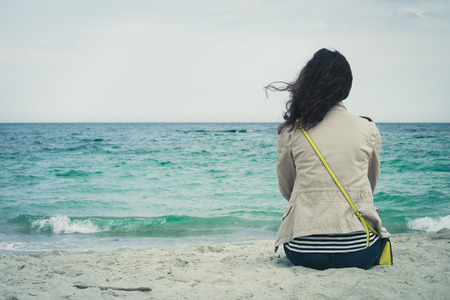 Young cute girl with curly hair sitting on an empty beach and looks at sea.