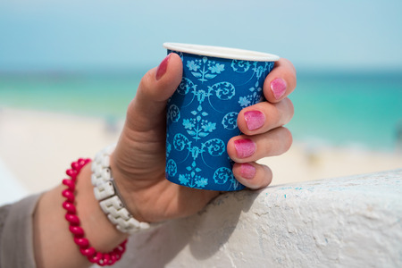 parapet: Blue cup of coffee in a female hand on a beach background. The hand rests on a white parapet. On the wrist white and red bracelets.