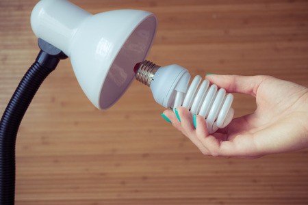 lamp: Installation of a modern economical bulb in a table lamp. Female hand holding spiral lamp.