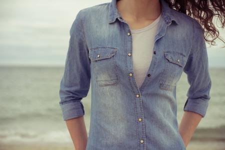 de vaqueros: Mujer delgada en una camisa de mezclilla y camiseta blanca se coloca en la playa contra el mar en tiempo nublado. Tiene el pelo rizado. Sus manos en los bolsillos. Colores retros. Acercamiento. Estado de �nimo relajado.