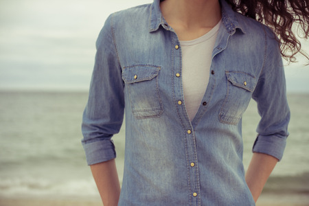 white shirt: Slim woman in a denim shirt and white tshirt stands on the beach against the sea in cloudy weather. She has curly hair. Her hands in her pockets. Retro colors. Closeup. Relaxed mood.