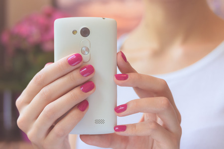 cameras: Mobile smart phone in female hands with a pink manicure on the background of pink flower and girl in a white T-shirt. Soft light.