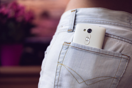 White mobile phone in the back pocket women's jeans on a purple background closeup. Standard-Bild