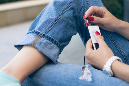 player bench: A young woman in jeans sitting on the bench and connect the headphones to her music player. White device is in female hands with a red manicure. Listening to music while walking. Photographed closeup.