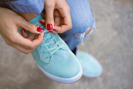 赤い女性の手は、スポーツ シューズに結ばれたひもをマニキュアします。彼女は靴紐を解き、野外を歩いている青いジーンズの若い女性。市内の散 写真素材