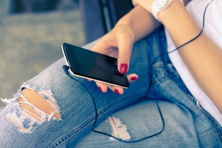 escuchar: Una mujer joven en pantalones vaqueros sentado en el banco y conectar los auriculares a su tel�fono m�vil. Tel�fono inteligente Blanca est� en manos femeninas con una manicura rojo. Escuchar m�sica mientras camina. Colores retros.