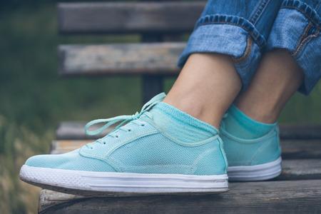 zapato: Pies femeninos en los pantalones vaqueros y zapatos deportivos. Zapatillas de deporte están en un banco de madera en un parque cerca. Mujer descansando en el banquillo después de la caminata.