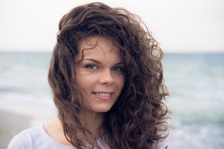 windy day: Portrait of a young cute smiling woman with brown curly hair close-up. Walking along the beach on a windy day. Good mood in the fresh air.