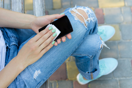 Hands of a young girl wipe mobile phone antibacterial cloth. A young woman in jeans sitting on the bench and wipe the screen of a modern mobile phone.