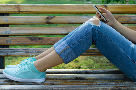 Legs of a young woman in jeans on a bench in the park. Girl resting in a park outdoors and uses a cell phone. Close-up.