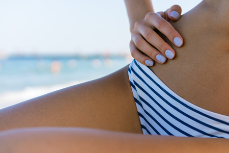 tanned body: Female slim tanned body in a swimsuit on the beach close-up on a background of blue water. Her hands with manicure.